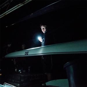 Crew member carrying boat at night