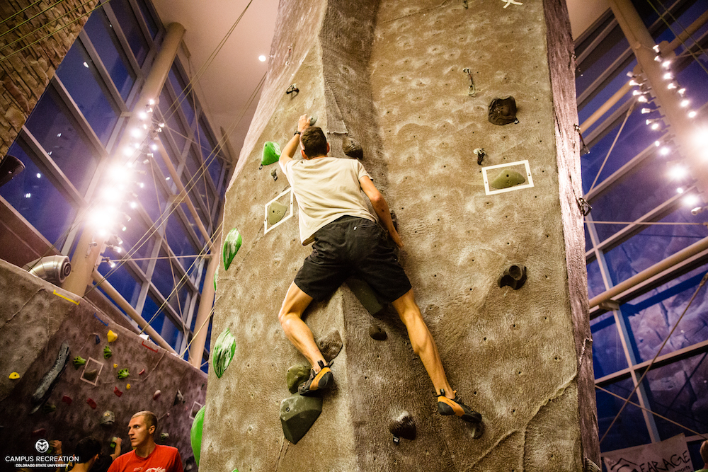 Indoor climbing wall participant scales the wall.