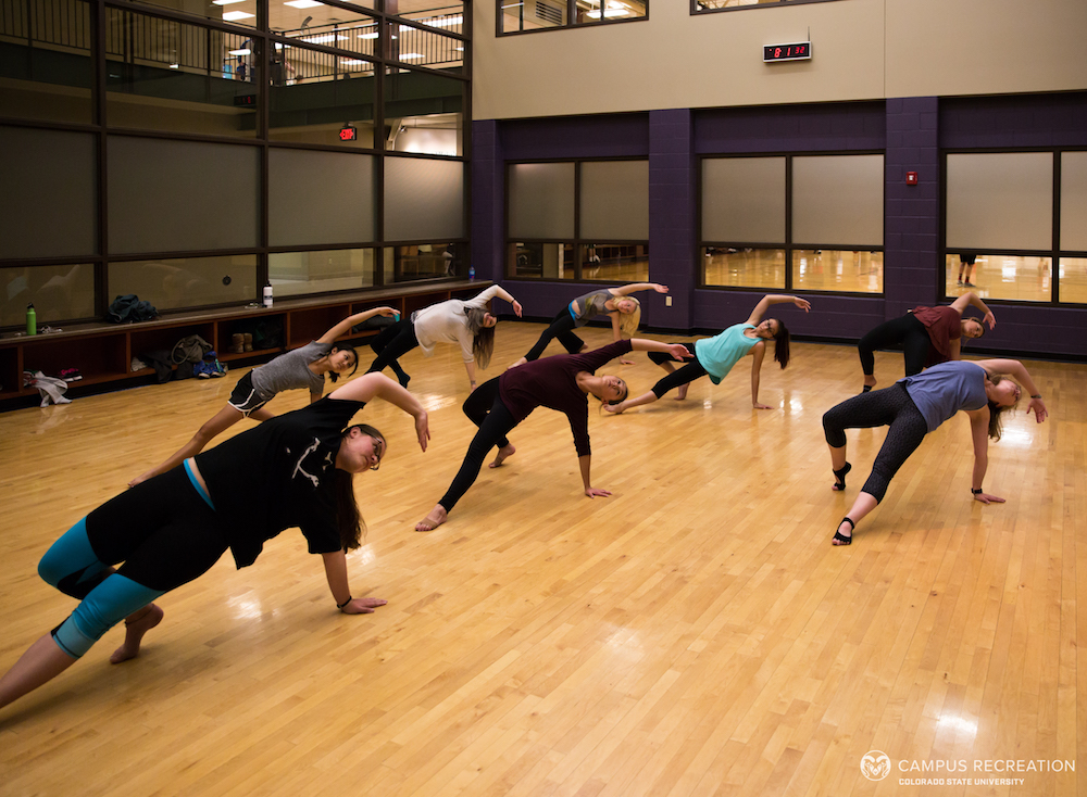 A photo of eight studio dance course participants demonstrating a floor move in the fitness studio