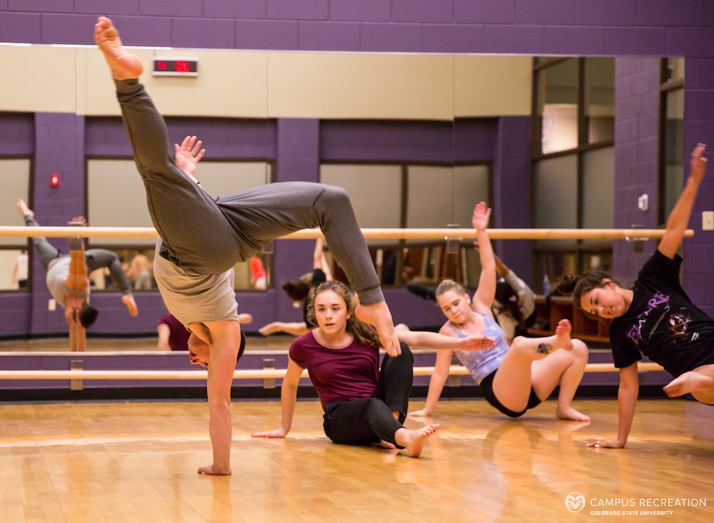A photo of participants in the Studio Dance course, watching as another student demonstrates a balance move on one hand
