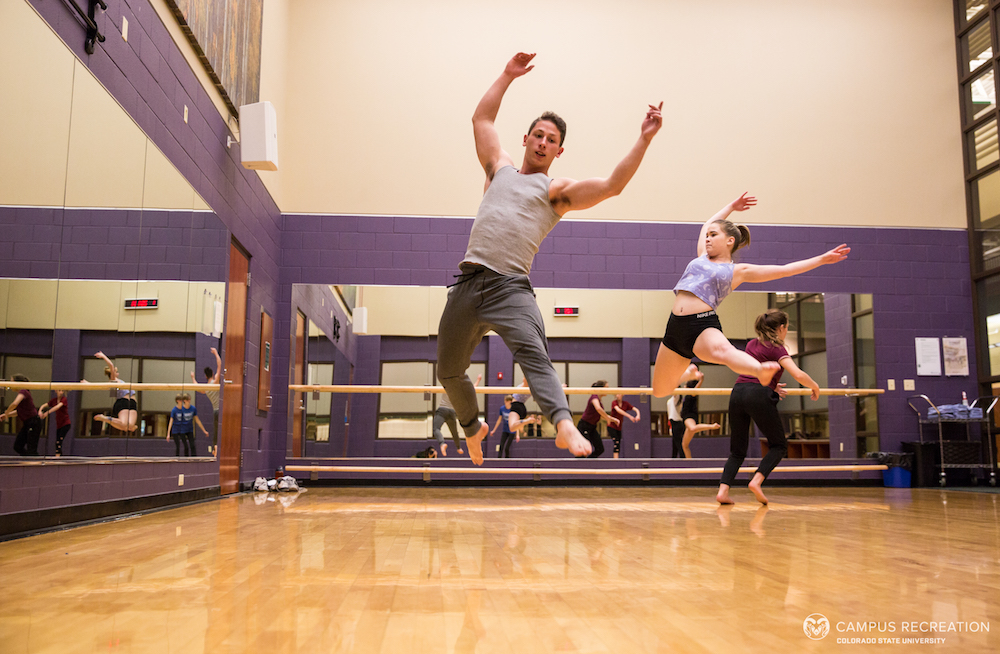 A photo of participants in the Studio Dance course, practicing leaps in the fitness studio