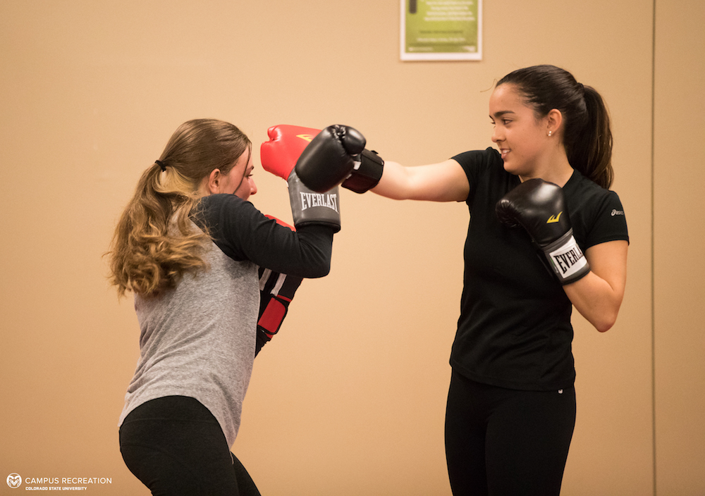 A photo of two participants in the Muay Thai martial arts course, practicing punches with boxing gloves on