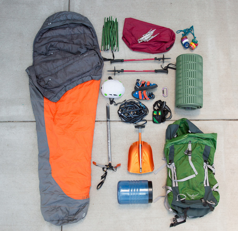 A photo displaying the various gear available for check-out from the CSU Outdoor Resource Room, including a sleeping bag, ice ax, sleeping pad, bear canister, hiking poles, and more