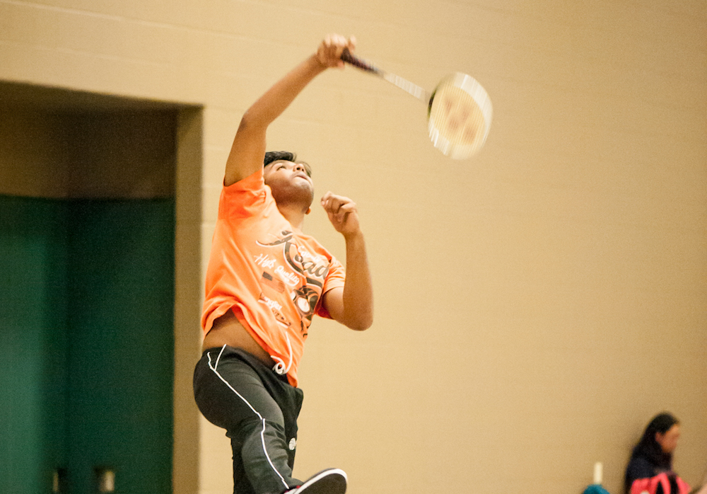 A racquetball participant serving a ball.
