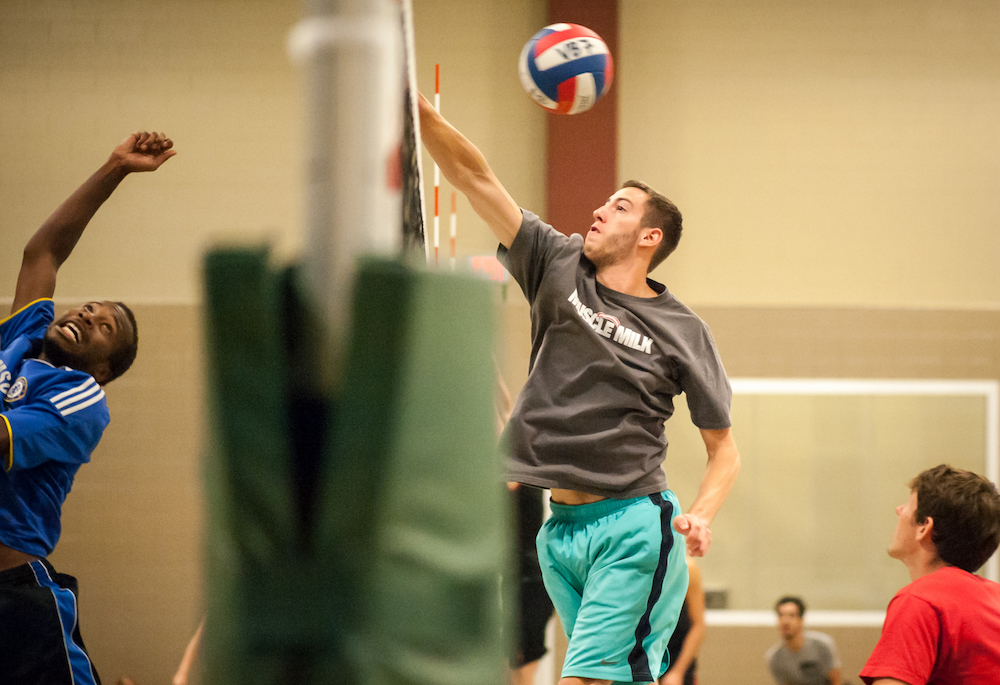 Volleyball participants spiking a ball over a net.