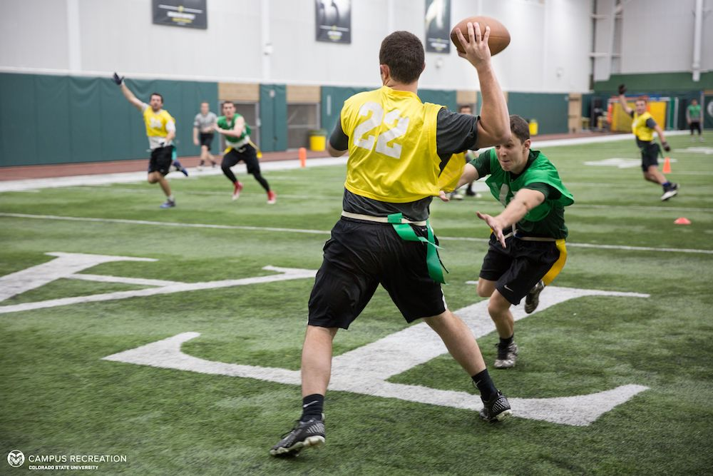 A photo of Intramural Flag Football participants, with one player passing the ball as another dives for their flags