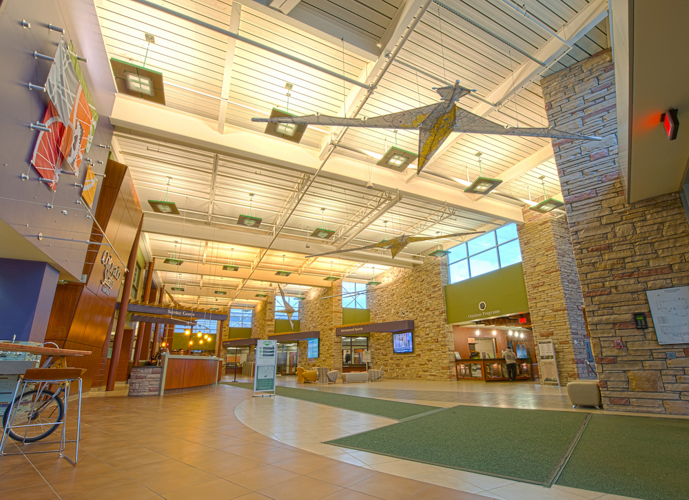 "A photo of the CSU Student Recreation Center lobby, showing the architectural stone work and large ""geese-like"" hanging structures"