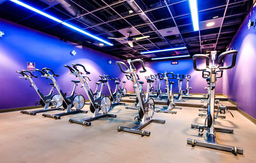 A photo of the cycling studio within the Student Recreation Center, which features purple walls, special lighting, and 20 stationary cycling bikes