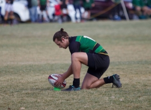 Participant holding rugby ball ready to punt.