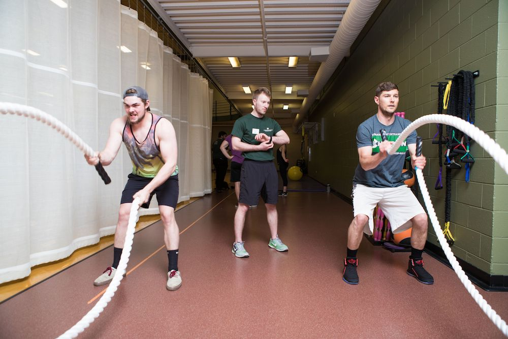 A photo of two Recreation Center patrons working out with the large battle ropes while a Personal Trainer looks on