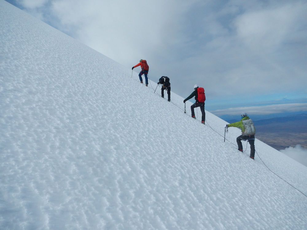 A group of participants summit a mountain in mexico on an outdoor trip.