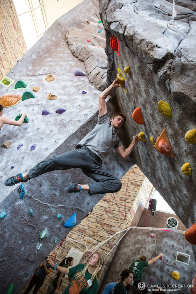 Male student hanging diagonally from the climbing wall