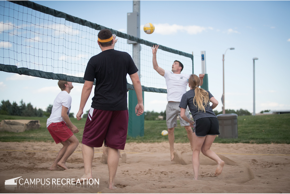 Action shot of students playing sand volleyball outside