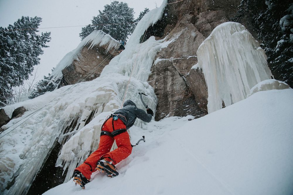 A participant summits a rock face while ice climbing.