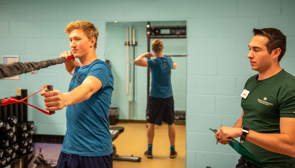 A personal trainer instructs a participant while using fitness bands.