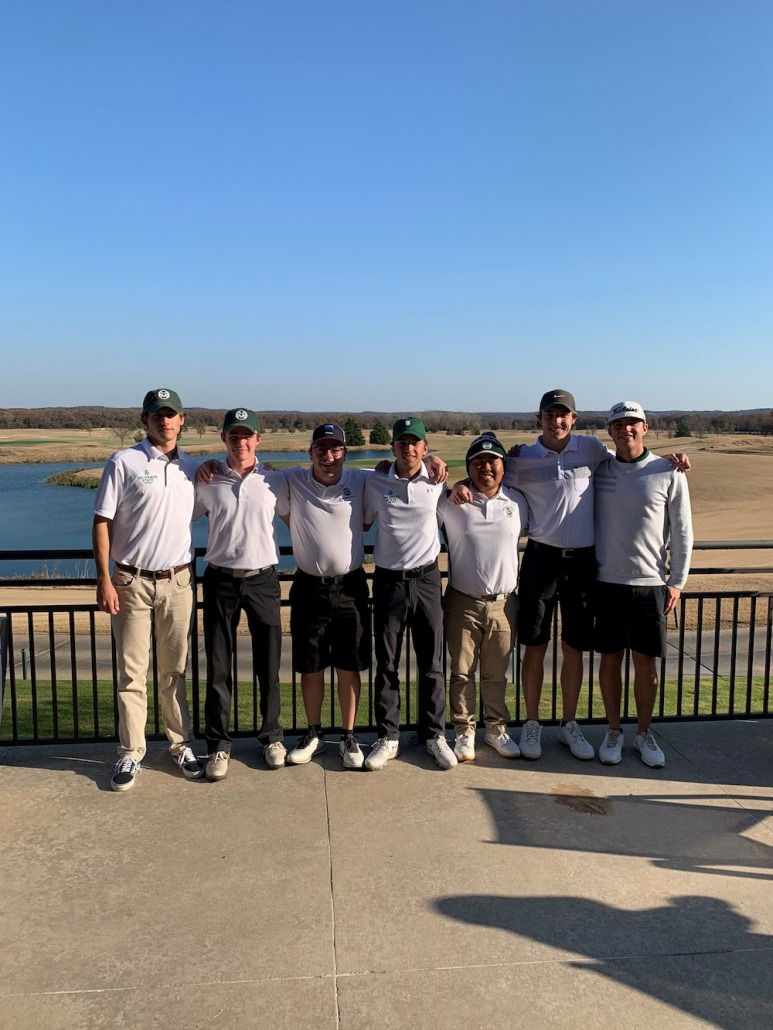 The CSU Golf team stand for a photo in front of a picturesque golf course.